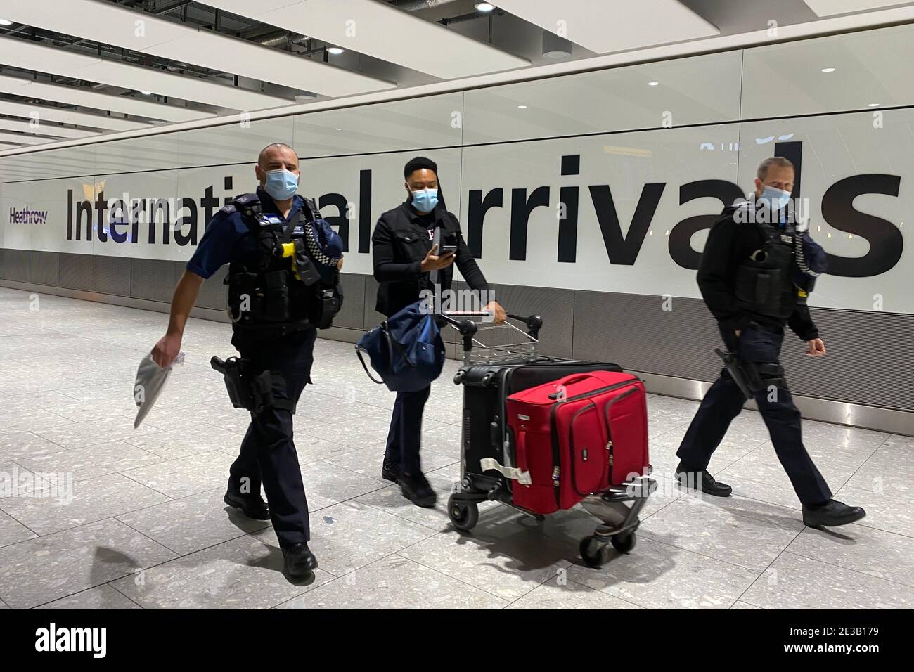 A passenger walks with police officers while pushing a trolley through the Arrival Hall of Terminal 5 at London's Heathrow Airport after arriving into the UK following the suspension of the travel corridors. Passengers arriving from anywhere outside the UK, Ireland, the Channel Islands or the Isle of Man must have proof of a negative coronavirus test and self-isolate for 10 days. Picture date: Monday January 18, 2021. Stock Photo