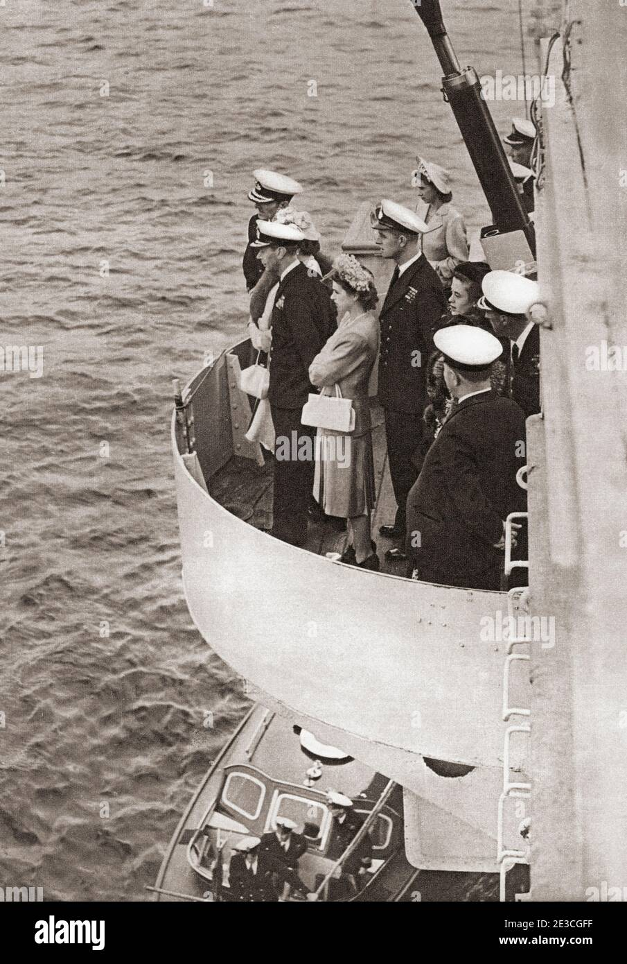 EDITORIAL ONLY Princess Elizabeth of York and Prince Philip, seen here when he was Lieutenant Philip Mountbatten, accompanying her father King George VI on board the H.M.S. Maidstone during an inspection of the Home Fleet in the Clyde.  George VI (Albert Frederick Arthur George),1895 –1952. King of the United Kingdom and the Dominions of the British Commonwealth.  Princess Elizabeth of York, future Elizabeth II, born 1926.  Queen of the United Kingdom.  Prince Philip, born Prince Philip of Greece and Denmark, 1921. Husband of Queen Elizabeth II of the United Kingdom.  From The Queen Elizabeth Stock Photo
