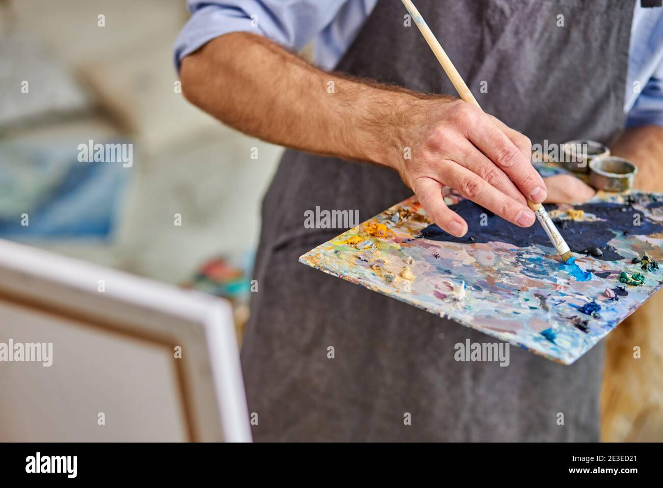 artist mix colors on palette holding in hand close up. creativity, art concept Stock Photo