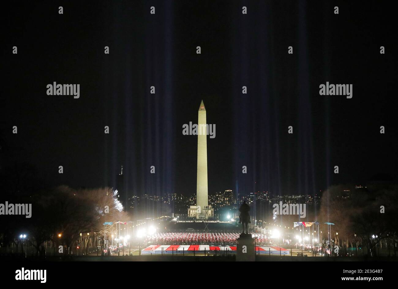 """Spotlights illuminate the sky from the """"field of flags"""" on the US national mall in honor of the upcoming inauguration of U.S. President-elect Joe Biden in Washington, U.S., January 18, 2021. REUTERS/Jim Bourg Stock Photo"""