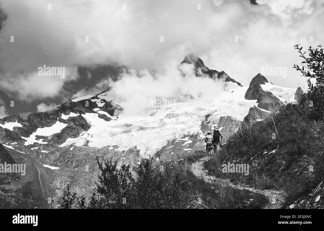 Father and son hiking in French Alps in summer. The Aiguille des Glaciers, mountain in the Mont Blanc massif. View From Chapieux valley, Savoie, Franc Stock Photo
