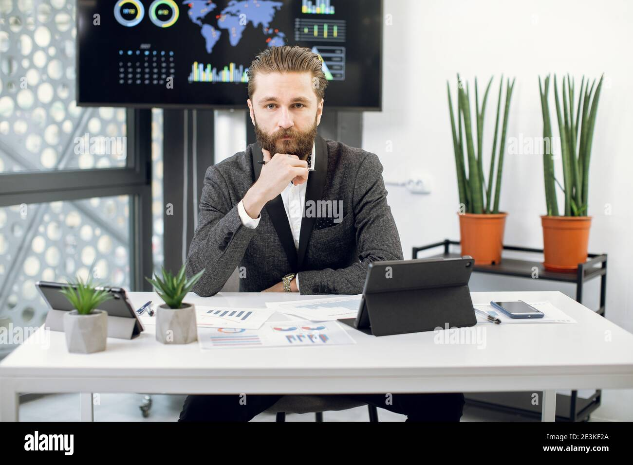 Handsome purposeful confident bearded businessman, chief executive officer in formal wear, sitting at workplace and looking at camera. Male worker Stock Photo