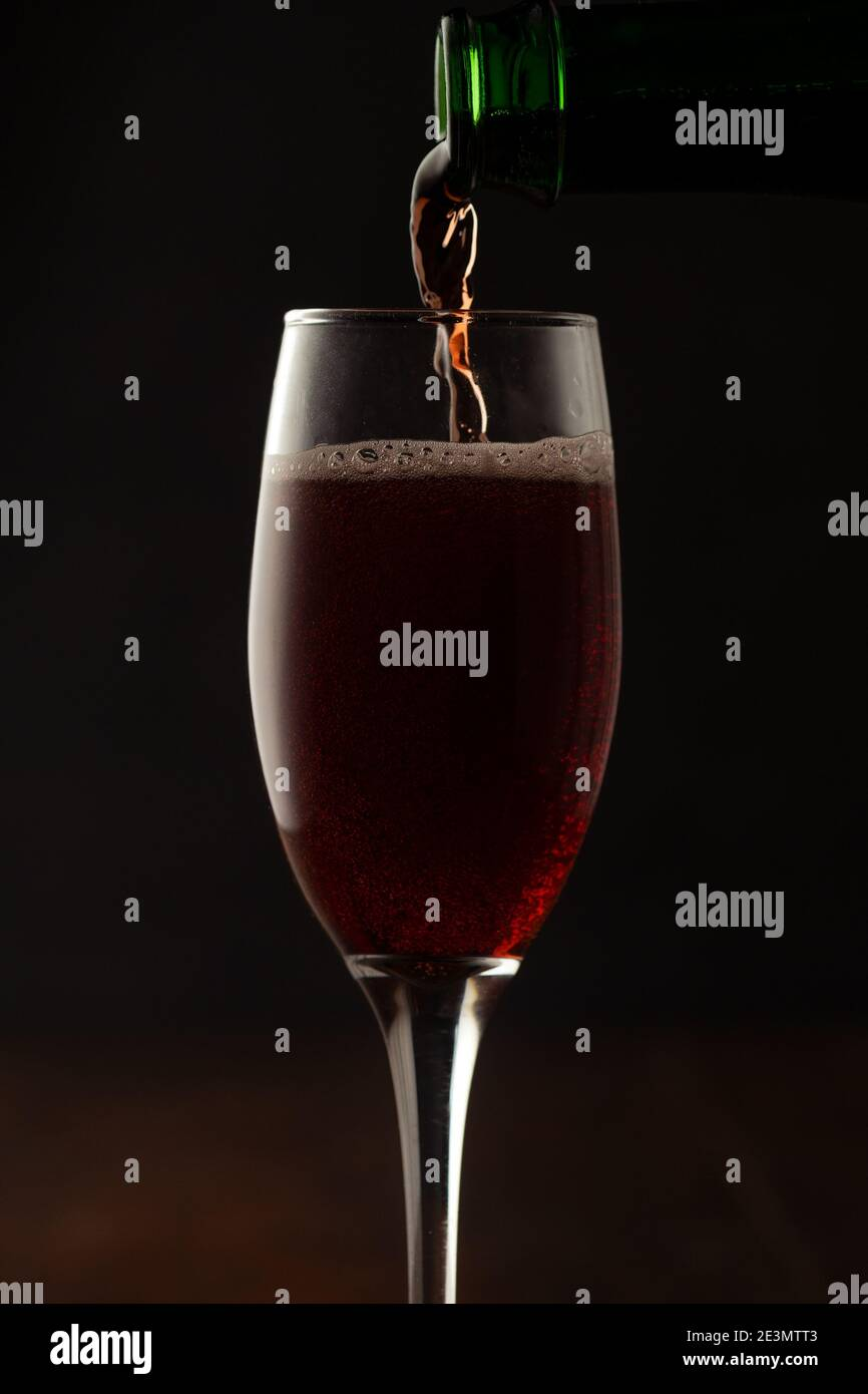 A glass of red wine with red wine bottle for celebrating party during New year evening Stock Photo