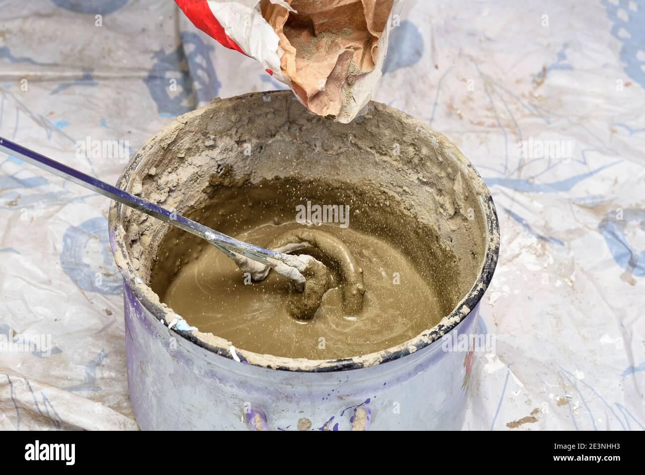 kneading cement mortar in saucepan. preparation for repair Stock Photo