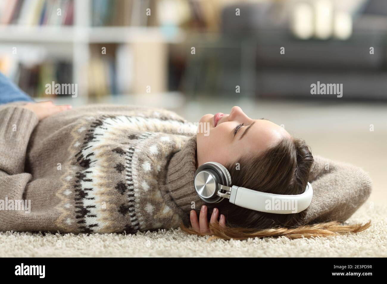 Relaxed teen listening to music wearing headphones lying at home in winter Stock Photo