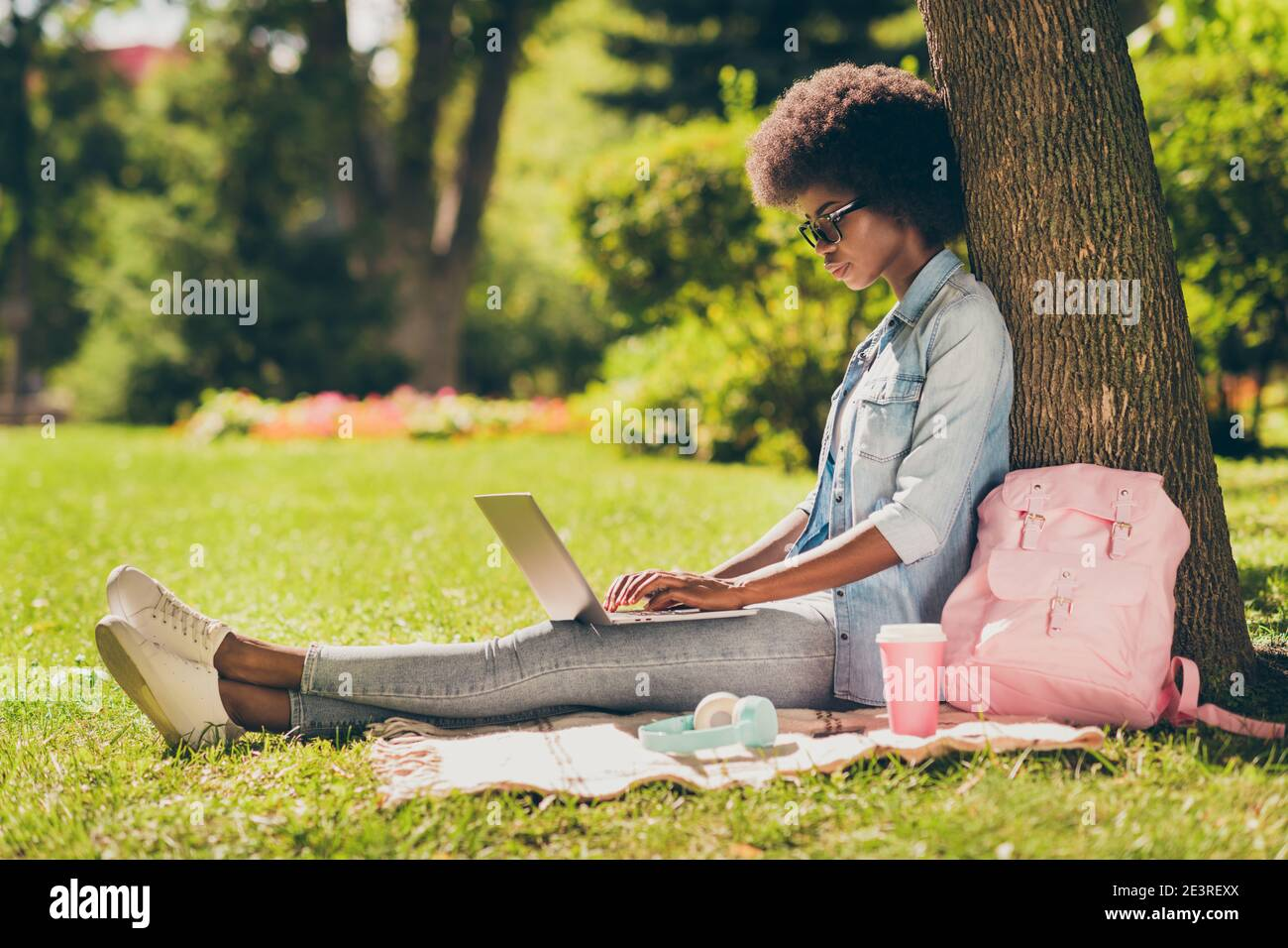 Full length body size side profile photo of black skinned woman with curly hair working on laptop browsing internet in city park Stock Photo