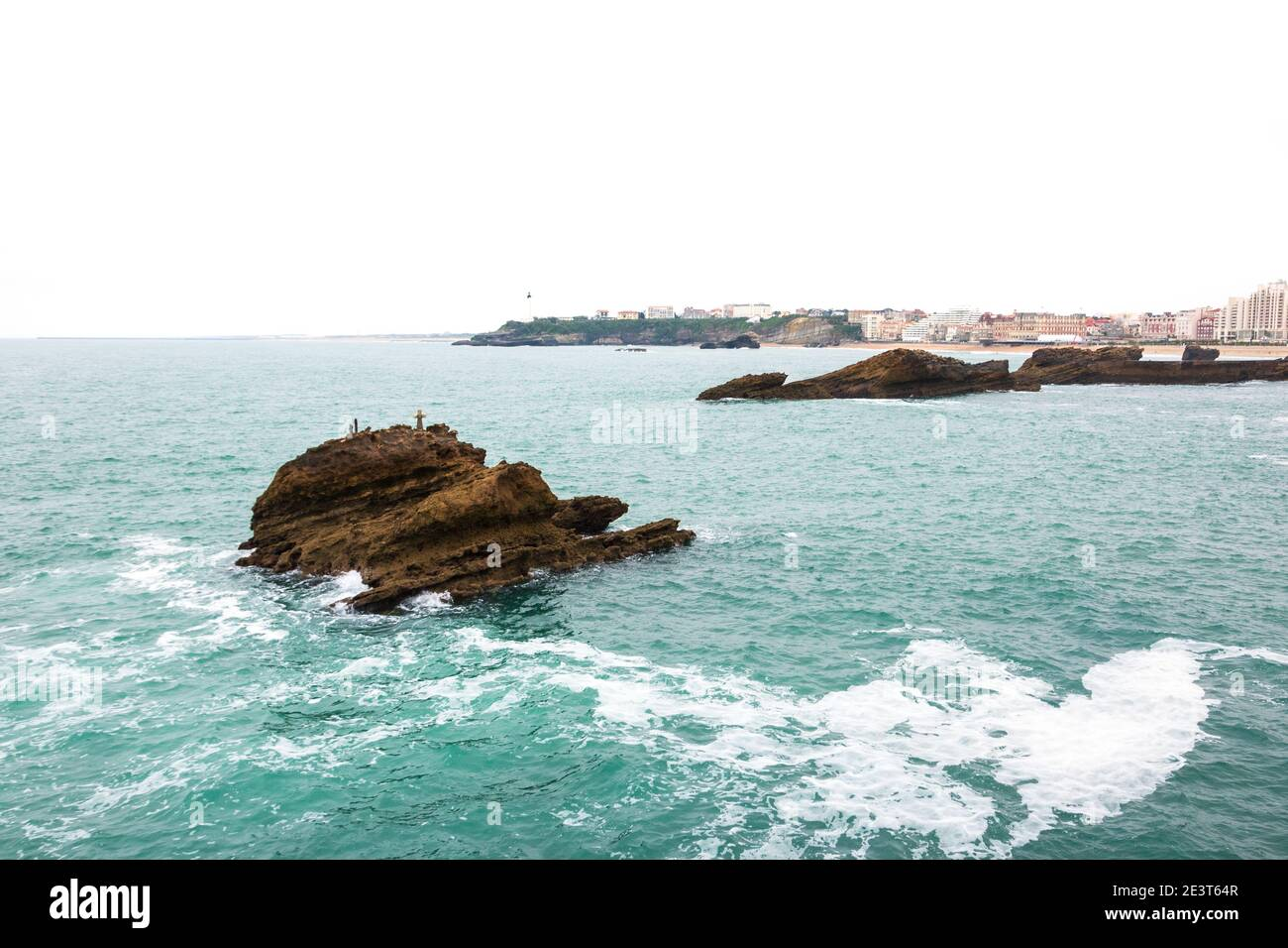 Biarritz (France). View from Rock of the Virgin Mary on rock with cross (commemorating drowned sailors) in the ocean water, city beach and lighthouse Stock Photo