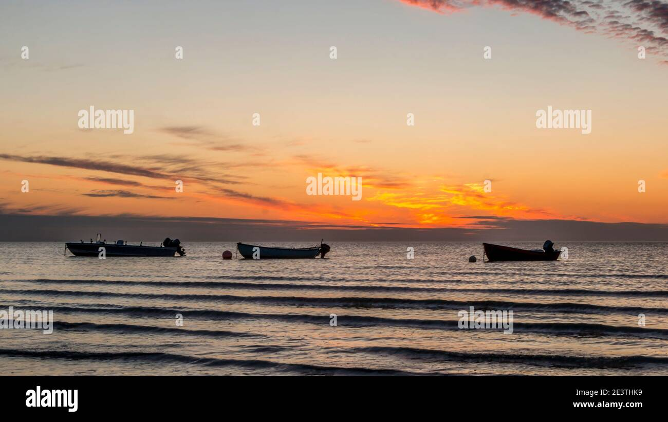 Beautiful sunset. pink, purple, golden, orange, blue colors over the sea. sky full of many colors. Boats in the water. Stock Photo