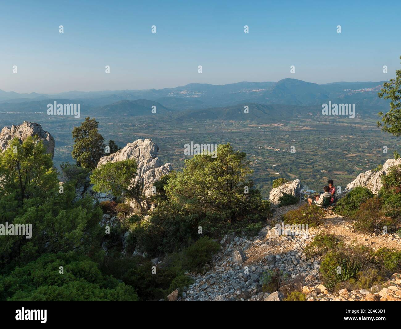 Baunei, Sardinia, Italy, September 17, 2020: Young happy couple having breakfast at Baunei viewpoint with green landscape of trees, limestone rocks Stock Photo