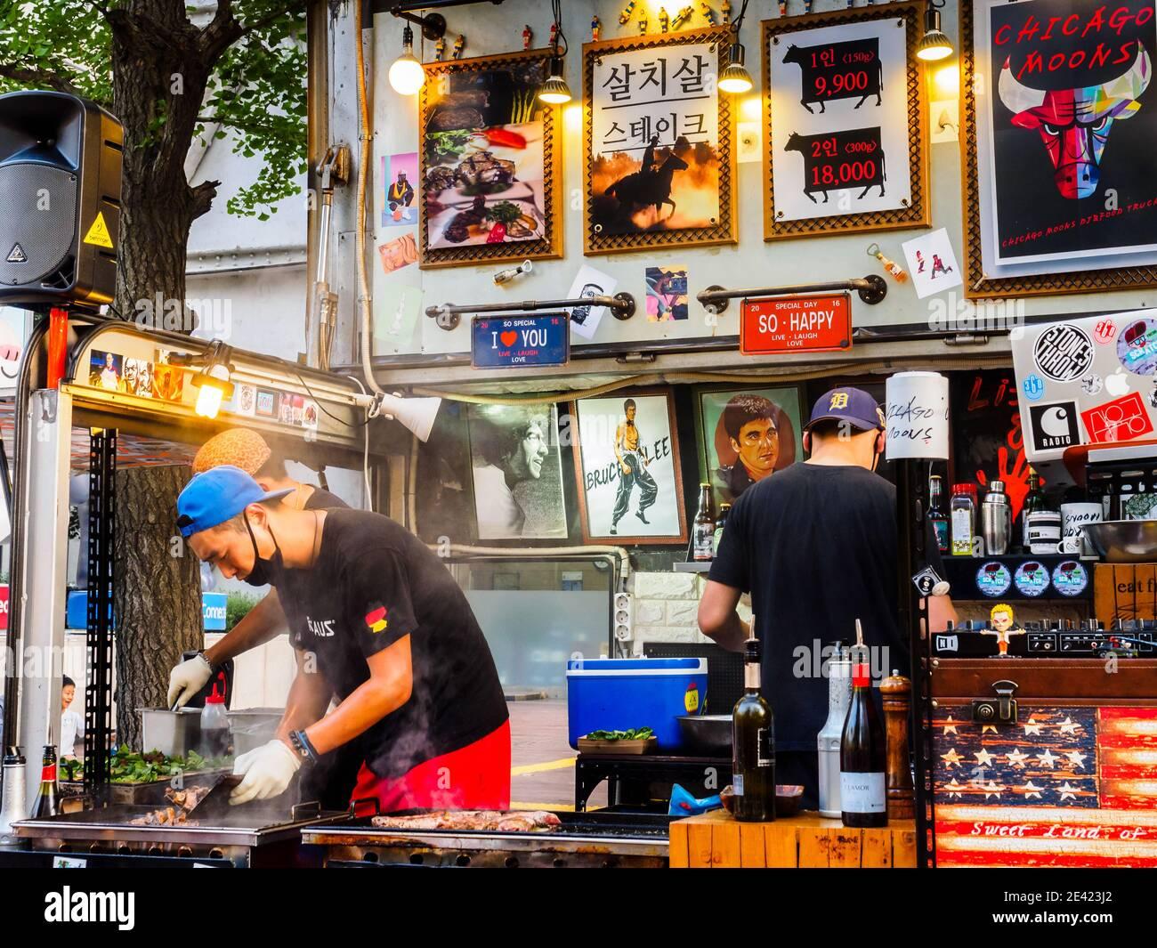 Seoul, South Korea - June 17, 2017: Vendors preparing fast food in the fast food kiosk at the street in Seoul. Stock Photo
