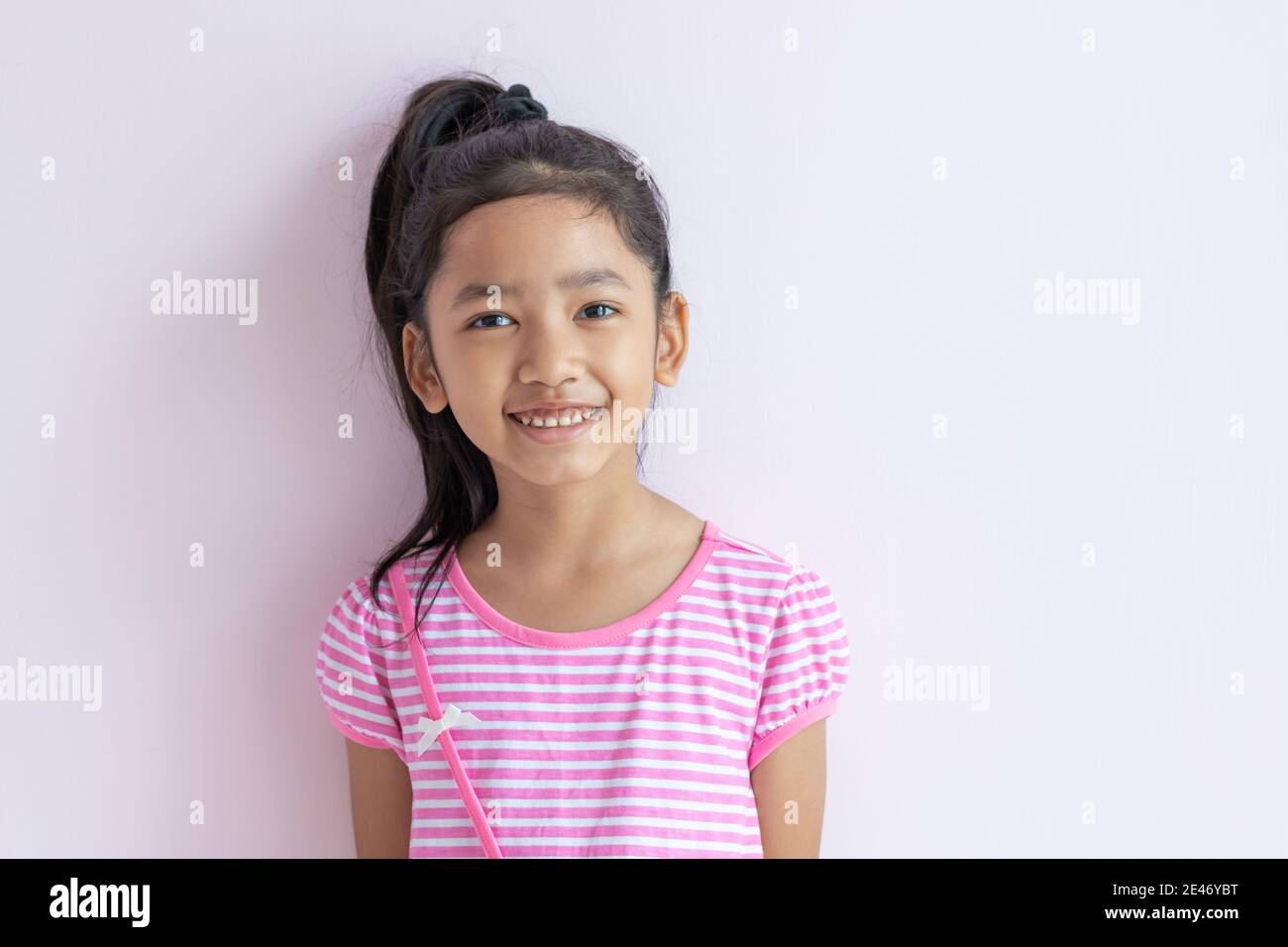 Portrait of an Asian little girl wearing a pink and white striped dress. The child tied up black hair and smiled with happiness. Stock Photo