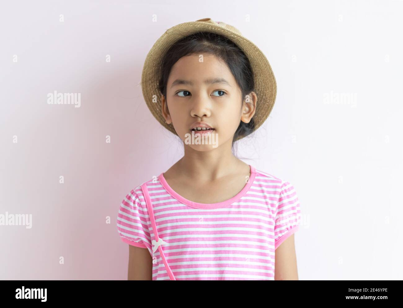 Portrait of an Asian kid wearing a pink and white striped dress. The girl wore a hat and looking to her side. Stock Photo