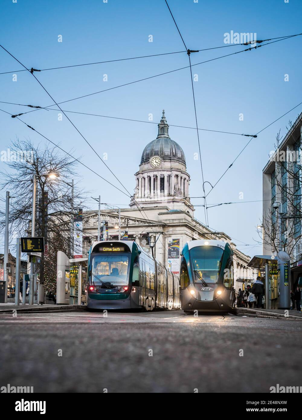 Nottingham UK city centre shoppers trams council house illuminated with tram parked in front lit up at night street lams and cables train waiting Stock Photo