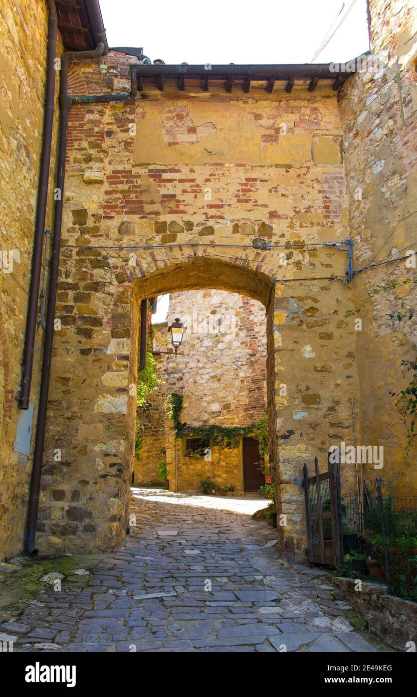 A stone archway across a quiet residential street in the historic medieval village of Montefioralle near Greve in Chianti in Florence province, Tuscan Stock Photo