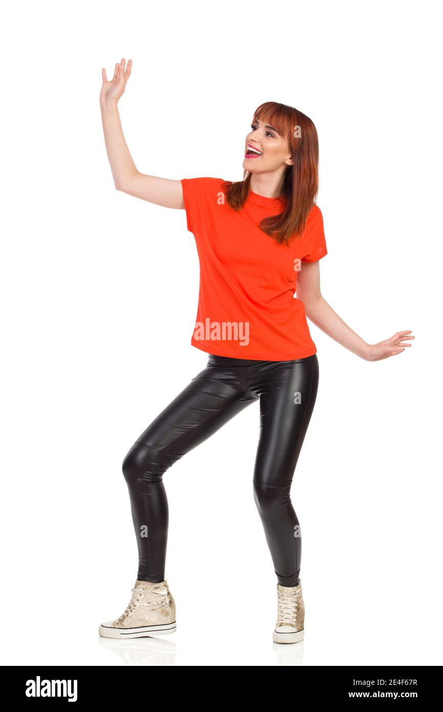Young woman in orange t-shirt, black leather pants and gold sneakers is dancing, looking away and shouting. Full length studio shot isolated on white. Stock Photo
