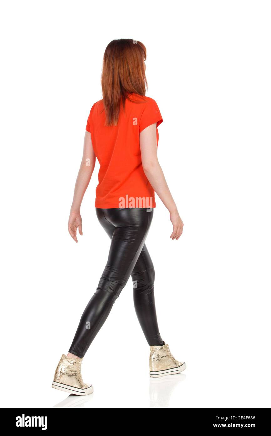 Young casual woman is walking. Full length studio shot isolated on white. Rear side view. Stock Photo