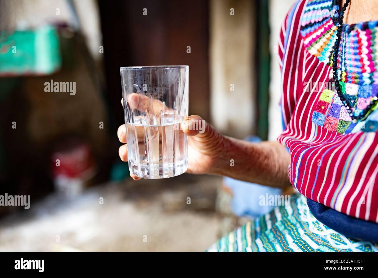 An elderly woman drinks a glass of clean water in San Juan la Laguna, Guatemala, Central America. Stock Photo
