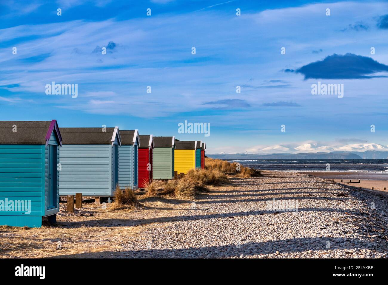 FINDHORN MORAY COAST SCOTLAND THE BEACH AND COLOURED CHALETS OR HUTS IN WINTER SNOW COVERED MOUNTAINS BEYOND Stock Photo