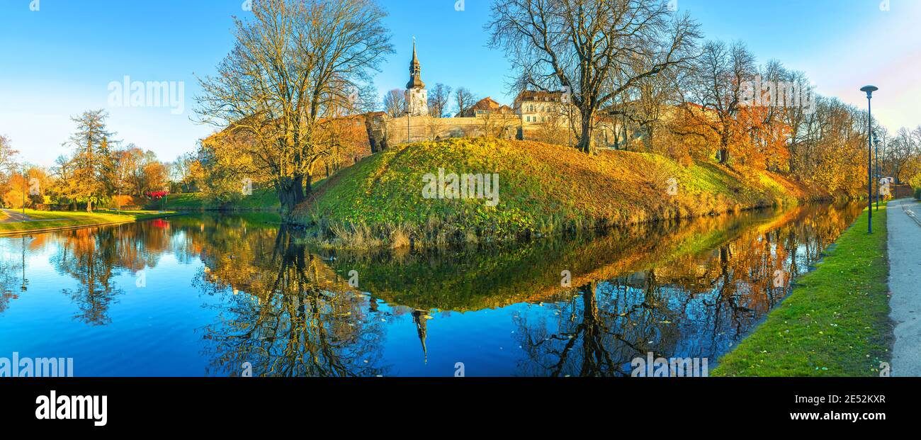 Panoramic landscape with park and pond along medieval city walls of Old Town at autumn time. Tallinn, Estonia Stock Photo