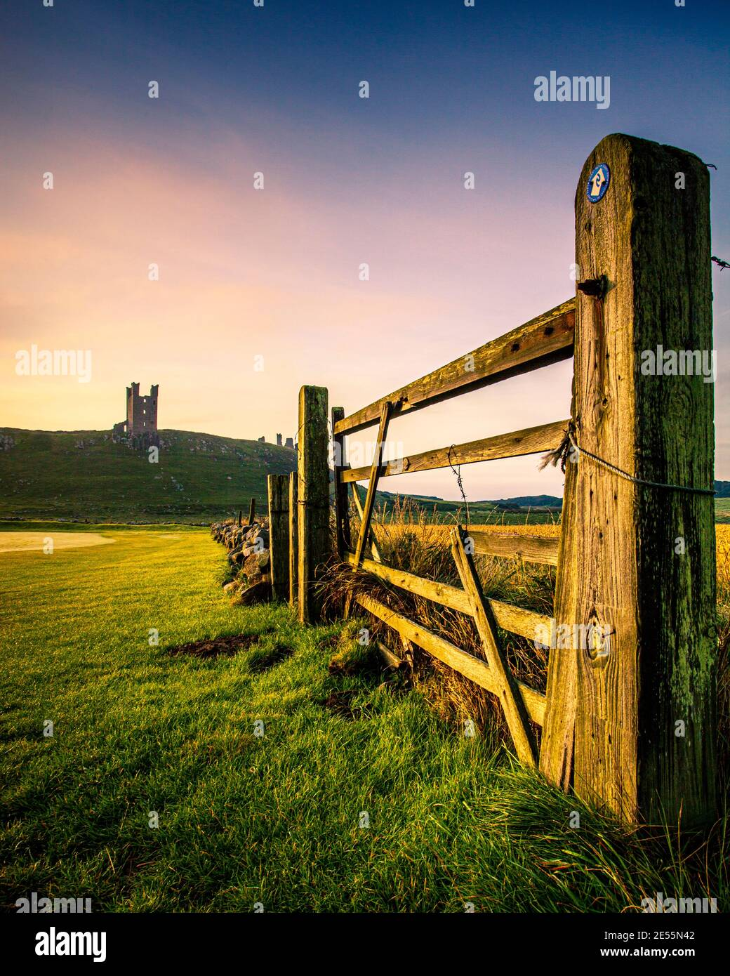Dunstanburgh castle in Northumberland viewed through a field gate. Stock Photo