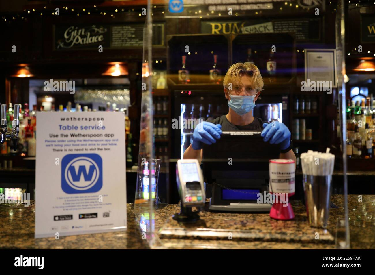 File photo dated 04/07/2020 of member of staff in PPE waiting to serve drinkers at the reopening of Wetherspoons' Toll Gate pub, in Hornsey, north London, as the coronavirus lockdown restrictions were eased across England. Saturday January 30 marks the one year anniversary of the earliest known death from coronavirus in UK. Issue date: Wednesday January 27, 2021. Stock Photo