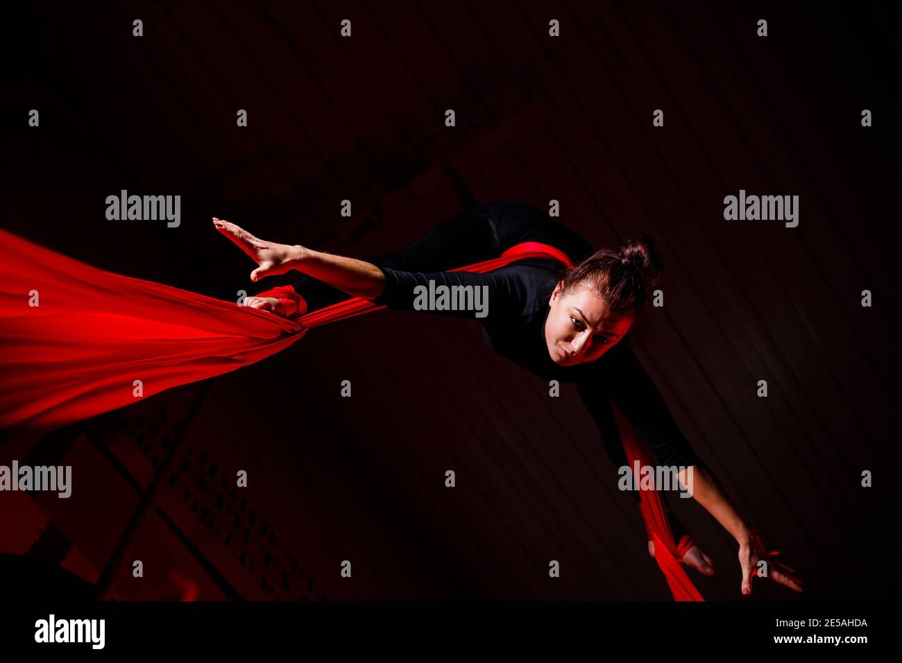 A sports girl performs gymnastic and circus exercises on red silk. Studio shooting on a dark background. Aerial gymnastics on canvas Stock Photo