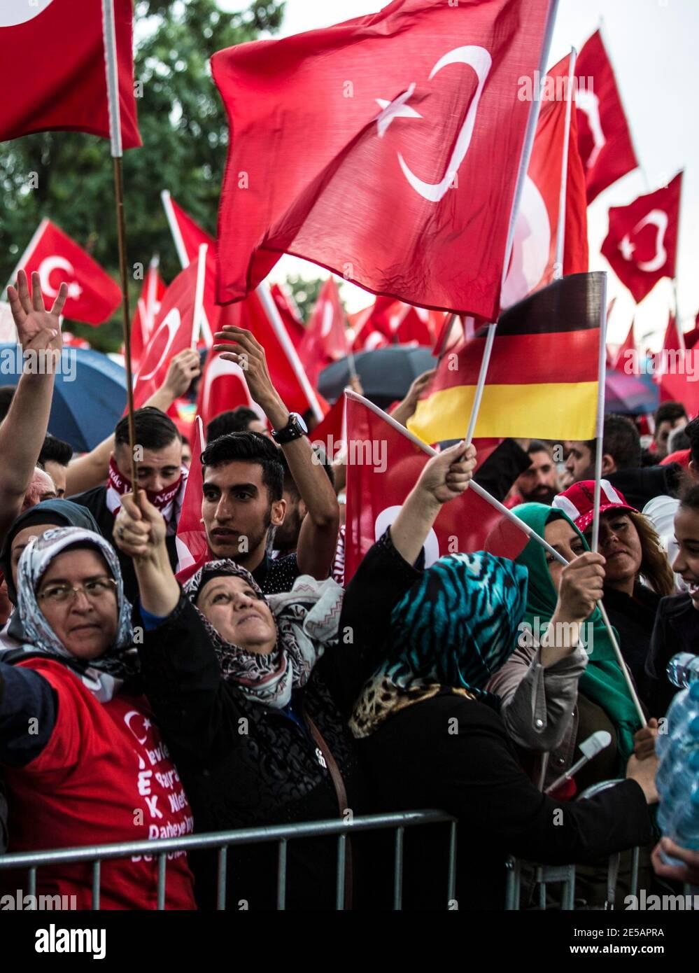 Ältere Frauen mit Kopftüchern schwenken türkische und deutscha Flaggen auf der Erdogan-Demonstration in Köln. Im Hintergrund deutsch-türkische junge M Stock Photo