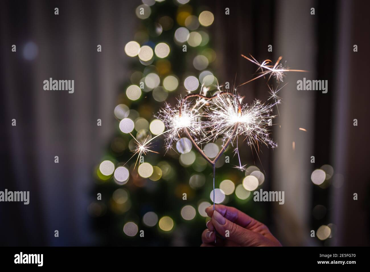 Bengal fire heart-shaped in the woman's hand burns against the background of a Christmas tree with colored garlands with bokeh Stock Photo
