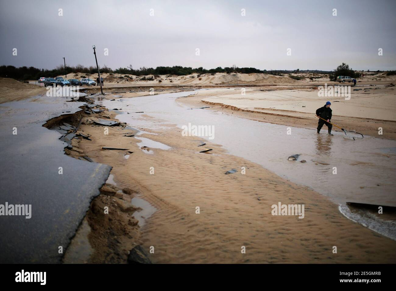 A man searches in a river stream following heavy rains and flooding on a beach of the Mediterranean sea near Kibbutz Nitzanim in southern Israel December 14, 2013. REUTERS/Amir Cohen (ISRAEL - Tags: ENVIRONMENT) Stock Photo