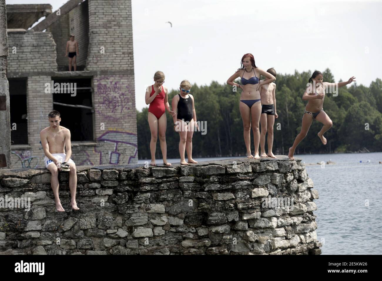 People jump into the water near Murru prison, an abandoned Soviet prison, in Rummu quarry, Estonia, during hot weather July 4, 2015. During the Soviet time, Rummu quarry was used as a mining site for Vasalemma marble and most of the workforce came from among the detainees of Murru prison. When the prison closed after 1991, pumps that once kept the quarry and the prison dry were shut down, causing water to fill the quarry. It has become an unofficial and unguarded swimming and diving spot, attracting locals and tourists. REUTERS/Ints Kalnins Stock Photo