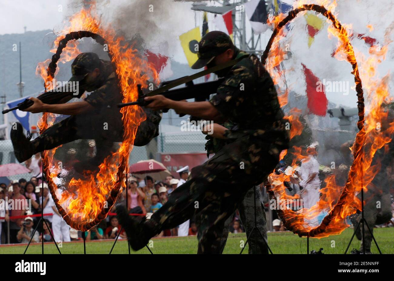 Chinese People's Liberation Army (PLA) soldiers jump through rings of fire in a war game as part of the show for the public during an open day at the Ngong Shuen Chau Naval Base on Hong Kong's Stonecutters Island July 28, 2012. The naval base was open to the public on Saturday, four days ahead of the PLA Army Day on August 1. REUTERS/Tyrone Siu (CHINA - Tags: POLITICS MILITARY) Stock Photo