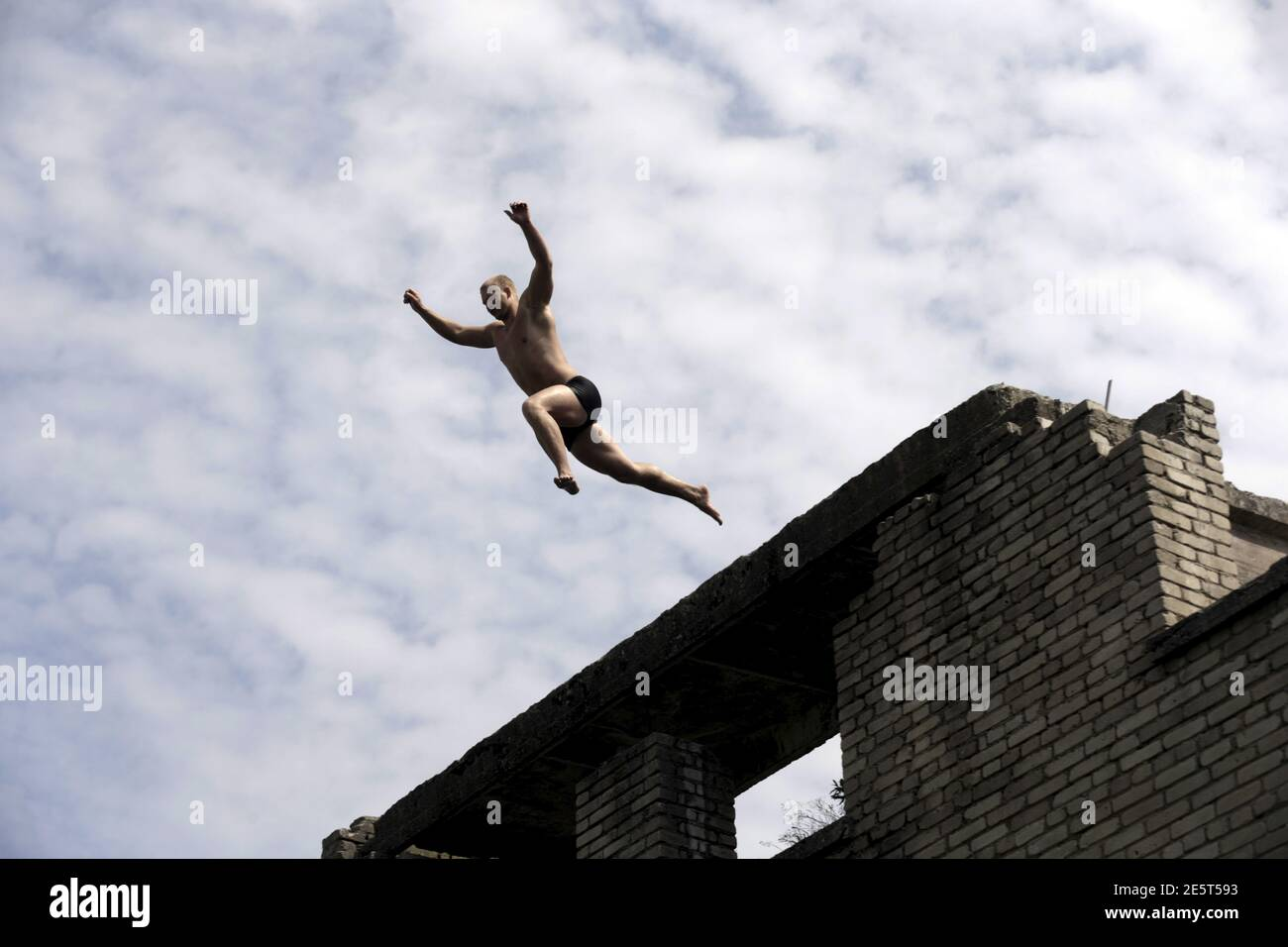 A man jumps into water from the roof of Murru prison, an abandoned Soviet prison, in Rummu quarry, Estonia, during hot weather July 4, 2015. During the Soviet time, Rummu quarry was used as a mining site for Vasalemma marble and most of the workforce came from among the detainees of Murru prison. When the prison closed after 1991, pumps that once kept the quarry and the prison dry were shut down, causing water to fill the quarry. It has become an unofficial and unguarded swimming and diving spot, attracting locals and tourists. REUTERS/Ints Kalnins Stock Photo