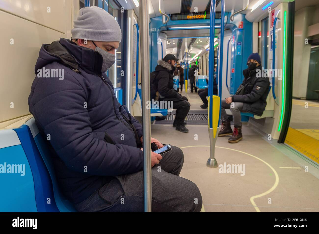 Montreal, CA - 24 January 2021: Passenger sitting in subway train, wearing face mask to protect from Covid-19 Stock Photo