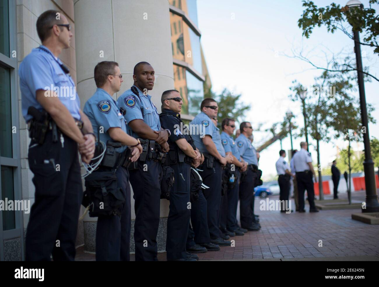 Police officers stand guard as demonstrators (not pictured) protest against the death of black teenager Michael Brown, outside St Louis County Circuit Clerk building in Clayton, Missouri August 12, 2014. Police said Brown, 18, was shot in a struggle with a gun in a police car but have not said why Brown was in the car. At least one shot was fired during the struggle and then the officer fired more shots before leaving the car, police said. But a witness to the shooting interviewed on local media has said that Brown had been putting his hands up to surrender when he was killed. The FBI has open Stock Photo