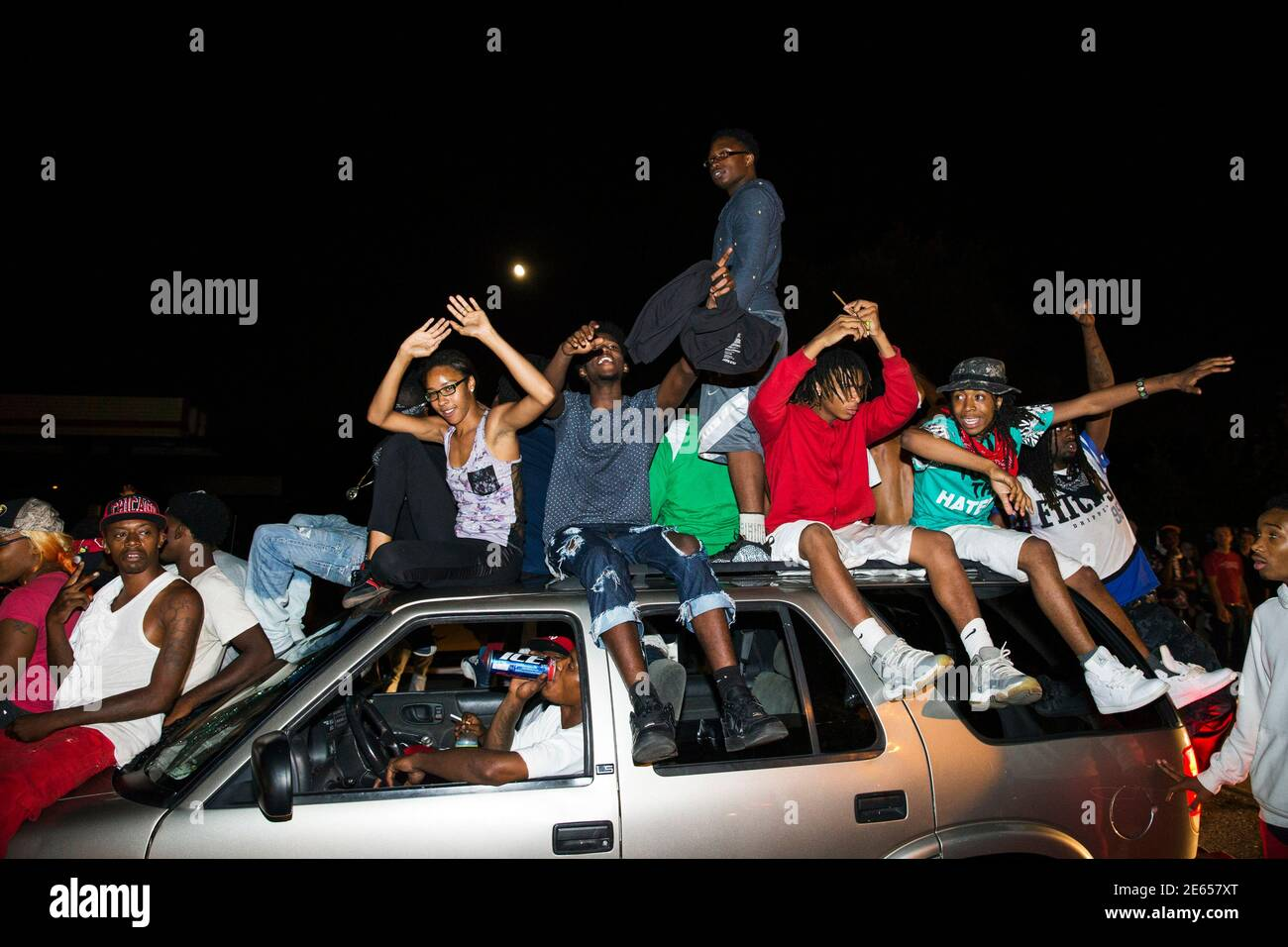 Protesters chant as they ride on a car during a peaceful demonstration as communities continue to react to the shooting of Michael Brown in Ferguson, Missouri August 15, 2014. Missouri's governor Jay Nixon moved to ease tensions on Thursday after days of racially charged protests over the police shooting of Brown, an unarmed black teenager, putting the African-American captain of the Highway Patrol Ron Johnson in charge of security in the St. Louis suburb of Ferguson. REUTERS/Lucas Jackson (UNITED STATES - Tags: CIVIL UNREST CRIME LAW) Stock Photo