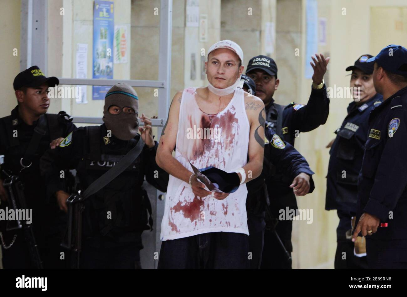 An injured gang member of the Mara 18 (M-18) is escorted by policemen after being checked by doctors at a hospital in Tegucigalpa August 3, 2013. Three gang members were killed and five more injured after members of the Mara 18 (M-18) clashed with members of rival gang Mara Salvatrucha (MS-13) at the maximum security jail of Tamara early Saturday, local media reported. REUTERS/Jorge Cabrera (HONDURAS - Tags: CIVIL UNREST CRIME LAW) Stock Photo