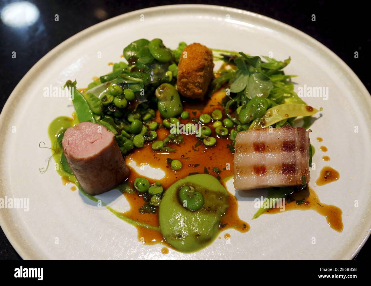 """A plate of Hungarian """"mangalica"""" pork prepared in three ways by a chef at Costes, the first restaurant to earn a Michelin star in Hungary, is seen in Budapest, Hungary, June 9, 2015. Mangalicas, which were all but extinct 25 years ago, now feature prominently in some of the best restaurants in the world for their meat, which gets its exceptional taste from the fat stored inside the muscle tissue. Picture taken June 9, 2015. REUTERS/Laszlo Balogh Stock Photo"""
