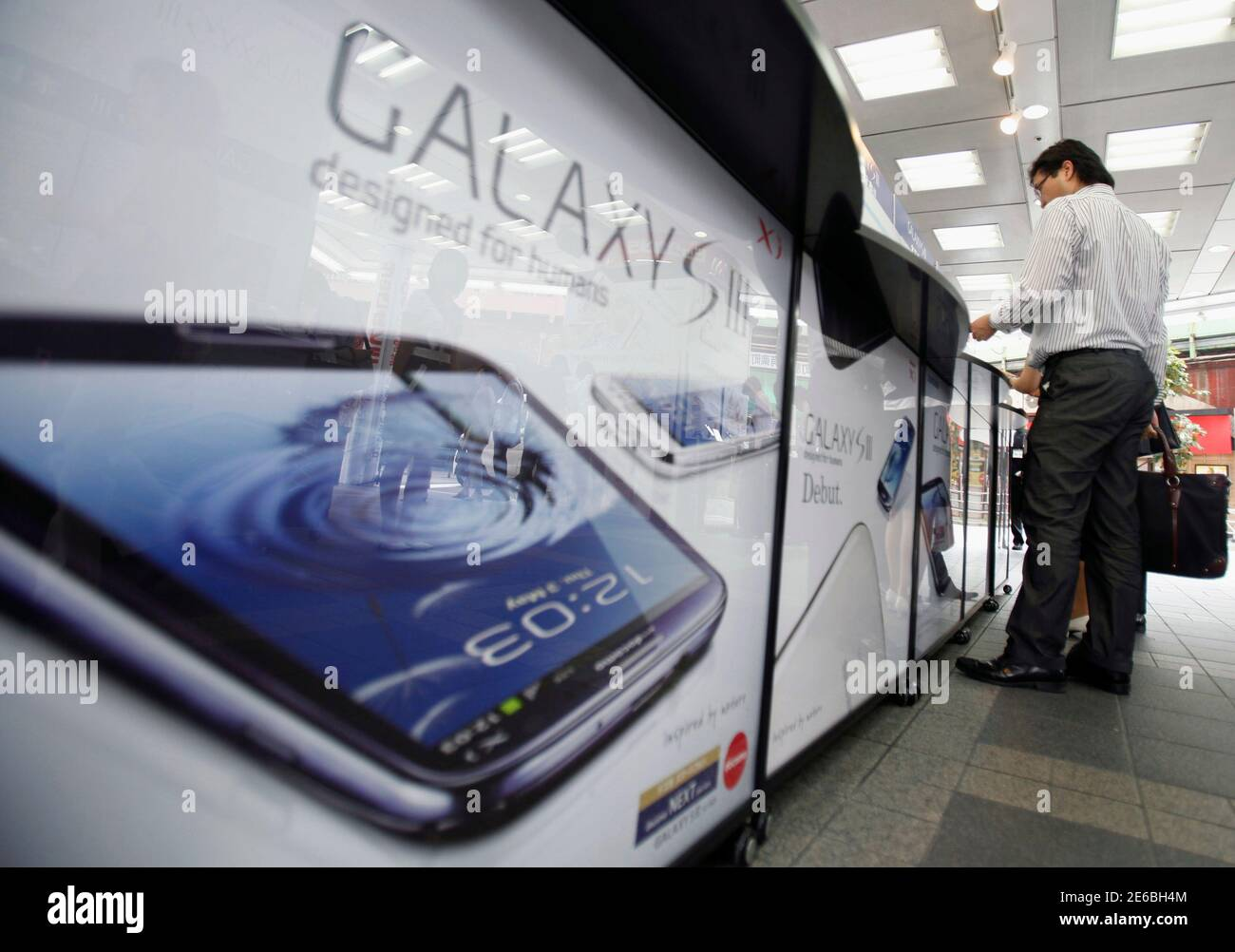 A customer tries out a Samsung Galaxy S III smartphone, released by Japan's largest mobile carrier NTT Docomo Inc, at an electronics store in Tokyo June 28, 2012. The Galaxy S III has received the most positive reviews among any of the Samsung smartphones, and the technology giant says the phone is on track to become its fastest selling smartphone, with sales likely to top 10 million in the first two months since its launch.   REUTERS/Yuriko Nakao (JAPAN - Tags: SCIENCE TECHNOLOGY BUSINESS TELECOMS) Stock Photo