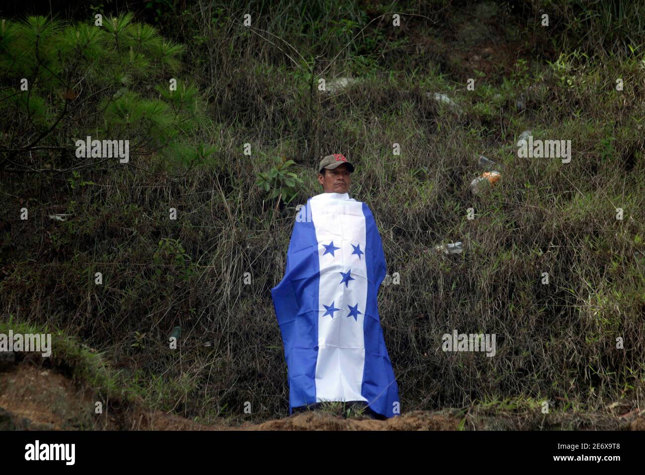 """A supporter of Honduras' ousted president Manuel Zelaya wraps himself with a Honduras flag during a protest on the outskirts of Tegucigalpa July 17, 2009. Venezuelan President Hugo Chavez said on Friday ousted Honduran President Manuel Zelaya would return to his country """"in the coming hours,"""" casting doubt on the outcome of mediation talks set for Saturday. REUTERS/Edgard Garrido (HONDURAS POLITICS) Stock Photo"""