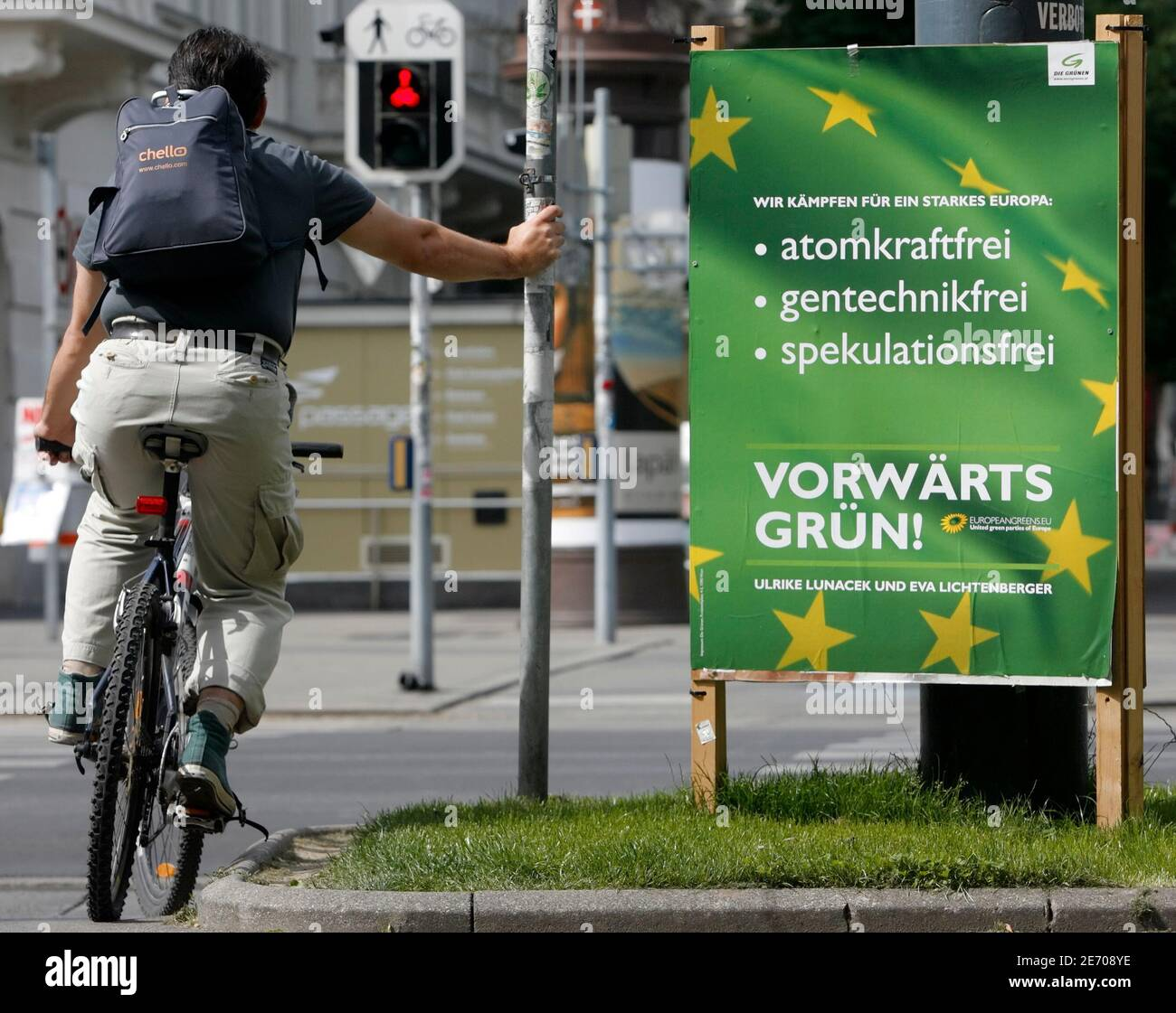 """A cyclist waits next to a Green party election campaign poster in Vienna May 22, 2009. """"Wir kaempfen fuer ein starkes Europa: Atomkraftfrei, gentechnikfrei, spekulationsfrei"""" reads """"We fight for a strong Europe: Without nuclear power, genetic engineering or speculation"""", """"Vorwaerts Gruen!"""" reads """"Green ahead!"""". REUTERS/Heinz-Peter Bader  (AUSTRIA POLITICS ELECTIONS) Stock Photo"""