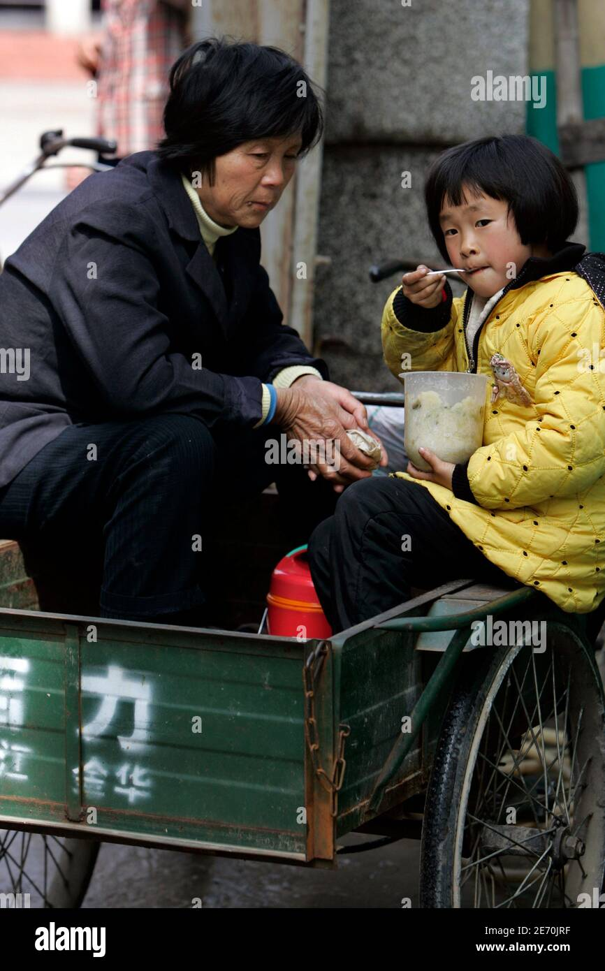 A girl and her mother eat lunch on a tricycle at a rural primary school in Nanhui district on the outskirts of Shanghai  March 2, 2007. After years of focus on urban schools and higher education, basic schooling in rural areas has finally become a priority for a government trying to address a rural-urban wealth gap in China that is contributing to social unrest. REUTERS/Aly Song (CHINA) Stock Photo