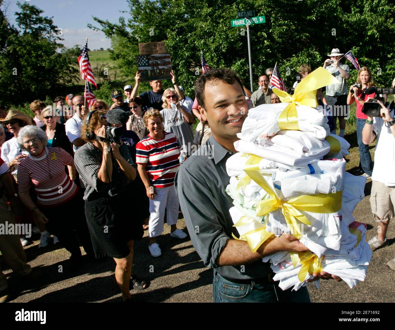 White House representative Bill Burck (R) carries more than a dozen folded bedsheets, each covered with handwritten messages supporting U.S. President George W. Bush, after Bush supporters (background) marched to his ranch in Crawford, Texas August 19, 2005. The goodwill visit by Bush supporters was in contrast to recent weeks of anti-war protests near the ranch by Cindy Sheehan, a mother whose son was killed last year in Iraq, demanding to meet with the President in an attempt to change his Iraq policy. REUTERS/Jason Reed  JIR/CCK Stock Photo