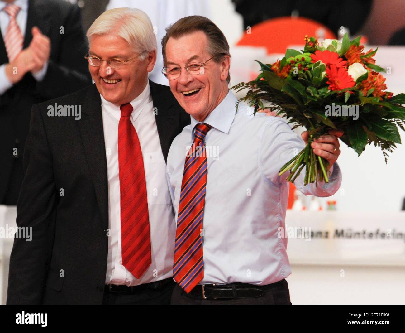Franz Muentefering (R) waves flowers after he was elected as leader of Germany's Social Democratic party SPD at a one-day party congress in Berlin October 18, 2008, while he stands with Foreign Minister Frank-Walter Steinmeier. Germany's Social Democrats crowned Steinmeier as their candidate for chancellor and elected Muentefering as their leader on Saturday.   REUTERS/Wolfgang Rattay    (GERMANY) Stock Photo