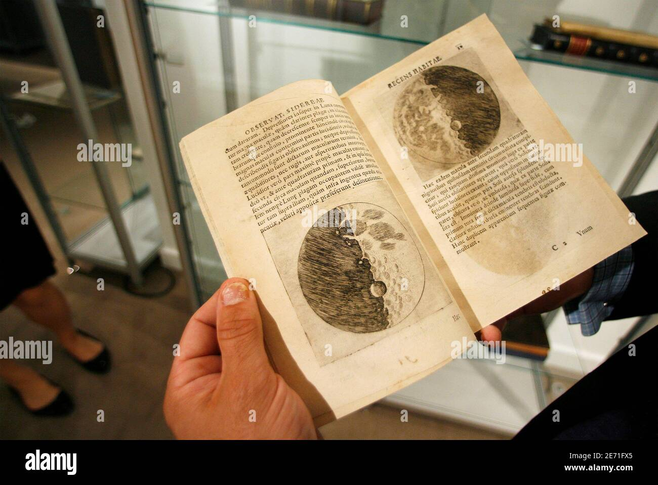Thomas Lecky, department head of books and manuscripts at Christie's, holds a book with sketches of the moon by Galileo Galilei during a preview at Christie's auction house in New York June 13, 2008.  REUTERS/Lucas Jackson (UNITED STATES) Stock Photo