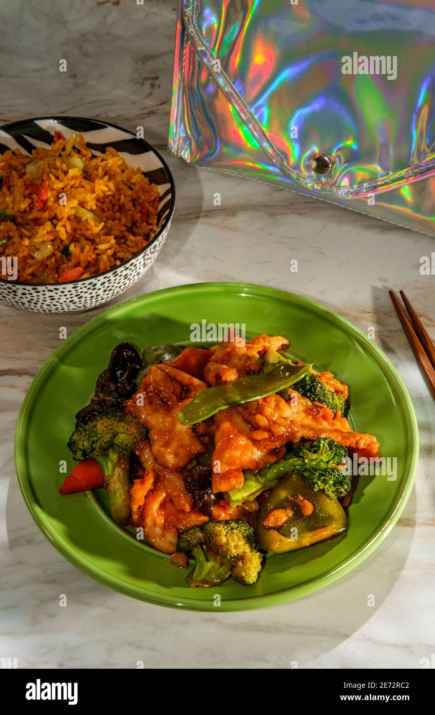 Chinese garlic chicken with sauteed mixed vegetables and side of pork fried rice Stock Photo