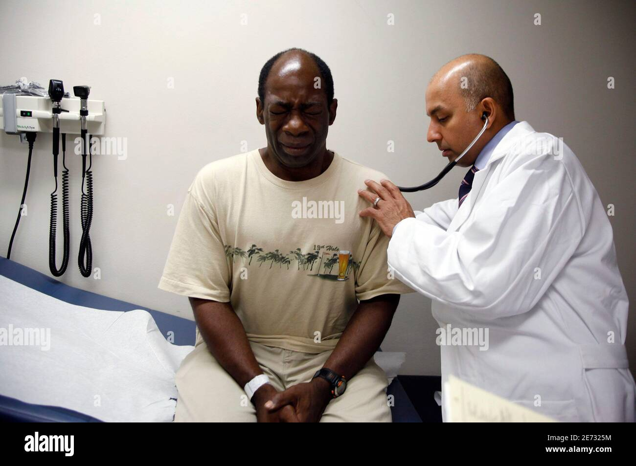 Ernest Sass, 52, (L) winces as he is attended to by Girish Bobby Kapur, M.D. (R) in a room used to see patients who don't require treatment for trauma inside the emergency room at Ben Taub General Hospital in Houston, Texas July 27, 2009.  Houston, the fourth-largest American city, is a case study in the extremes of the U.S. healthcare system.  It boasts the immense medical center that offers top-notch care at its 13 hospitals, but also has a higher ratio of uninsured patients than any major U.S. city: about 30 percent. To match feature USA-HEALTHCARE/TEXAS   REUTERS/Jessica Rinaldi (UNITED ST Stock Photo
