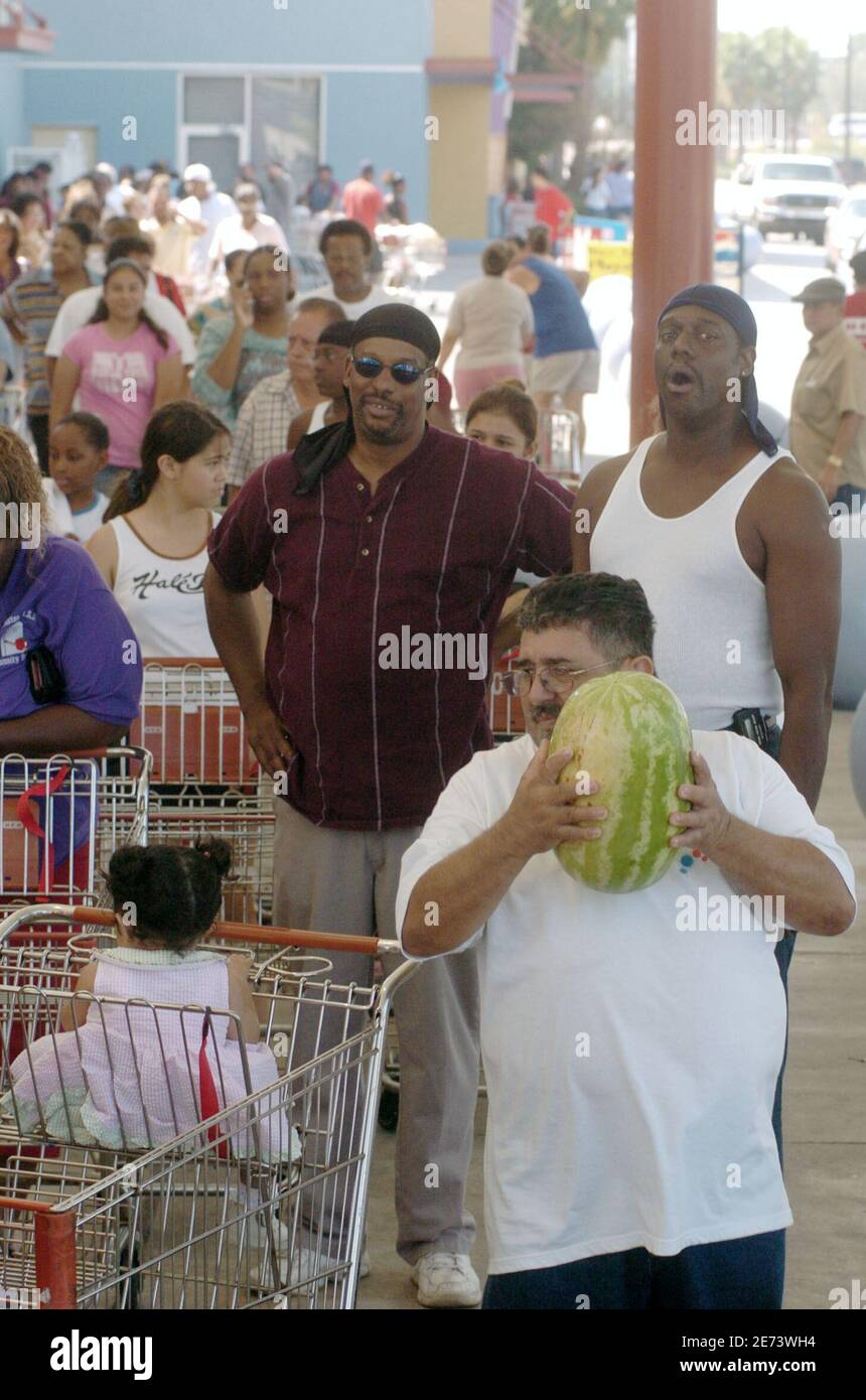 An unidentified man picks up a watermelon as he waits in a long line that surrounds the HEB Gulfgate Grocery store in Houston, Texas, September 25, 2005. The store opened on Sunday morning and it is the first time shoppers have had a place to shop since Hurricane Rita. Rescue teams hunted for people stranded in Louisiana's flooded Cajun country on Sunday, but officials expressed relief there was no major loss of life and that Hurricane Rita had largely spared the region's huge refineries. REUTERS/Tim Johnson Stock Photo