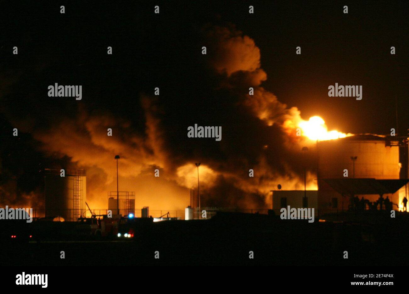 Albanian firefighters try to contain a fire at a fuel depot in the port city of Shengjin, some 70 km (44 miles) northwest of the capital Tirana, December 17, 2006. Firefighters worked all Sunday using retardant foam water and sand to prevent the fire from spreading to two bigger depots.   REUTERS/Arben Celi Stock Photo