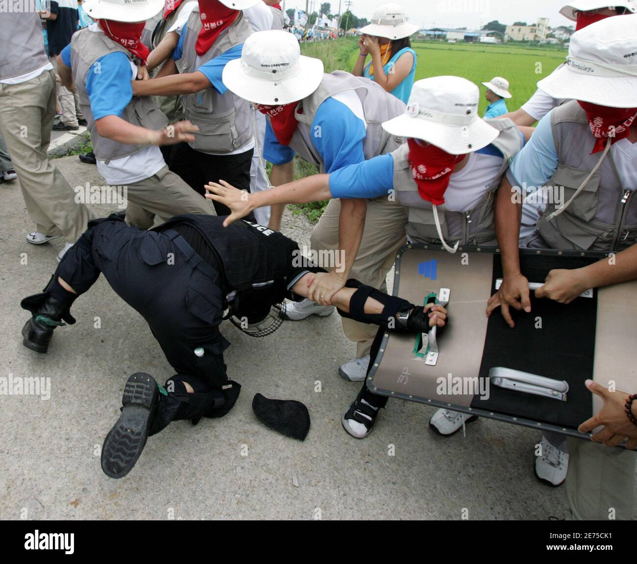 Protesters detain a riot policeman as police use shields and clubs to stop protesters trying to enter U.S. army's Camp Humphreys in Pyongtaek, South Korea.  Protesters detain a riot policeman as police use shields and clubs to stop the protesters trying to enter the U.S. army's Camp Humphreys in Pyongtaek, about 80 km (50 miles) south of Seoul, August 8, 2005. About 500 South Korean protesters from labour unions and college students' groups rallied near the U.S. army base on Monday as they demanded U.S. forces leave the country, which they insist block the reunification of the two Koreas. REUT Stock Photo