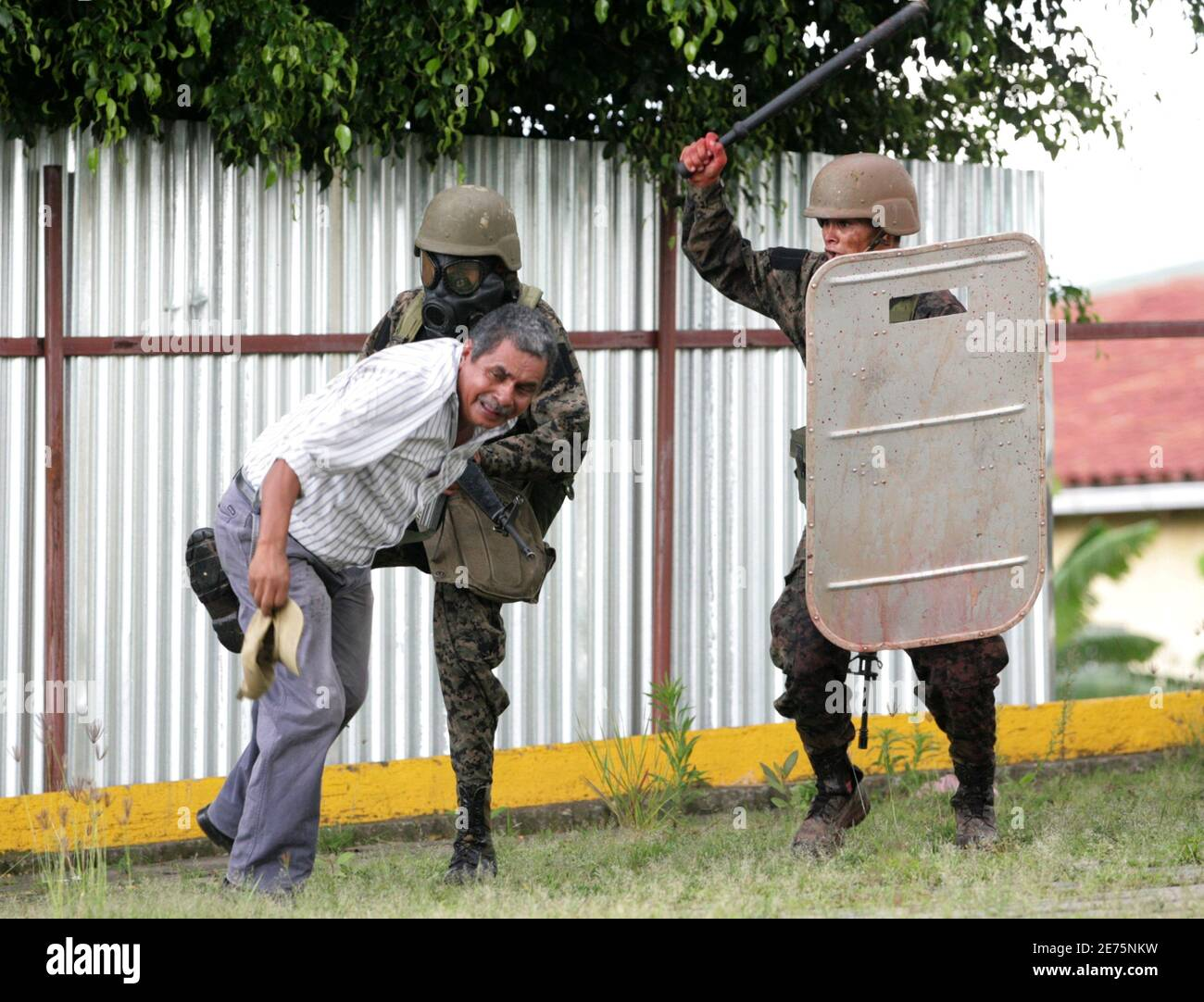 Soldiers attack a supporter of Honduras' ousted President Manuel Zelaya in Tegucigalpa June 29, 2009. Some 1,500 protesters, some of them masked and carrying sticks, taunted soldiers and burned tires just outside the gates of the presidential palace in a face-off with security forces. Honduras came under pressure on Monday to reinstate Zelaya as many Latin American leaders agreed to withdraw envoys. REUTERS/Oswaldo Rivas  (HONDURAS POLITICS CONFLICT) Stock Photo